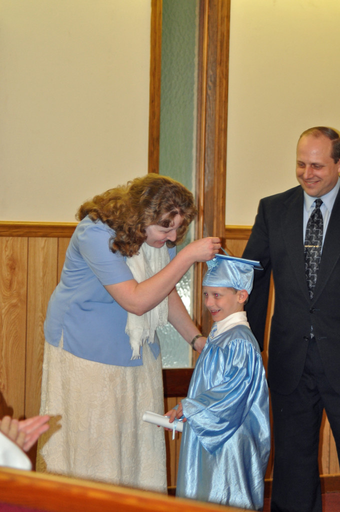 Seth Proctor receiving his diploma and moving of tassel by his parents Bro. Travis and Sis. Caroline Proctor.