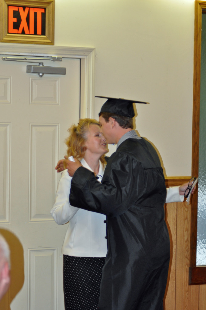 Mr. Adam Hewett receiving his diploma from his parents Sis. Shelly Hewett.