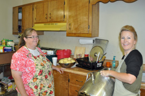 Mrs. Shelly doing the never ending job of dishes and Mrs. Toni observing her work or is she just taking a break from peeling potatoes?
